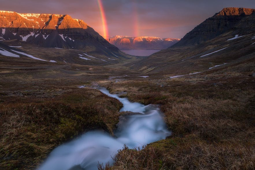 A river winds through the landscape leading to a double rainbow in the background - Iceland Photography | Everything You Need To Know