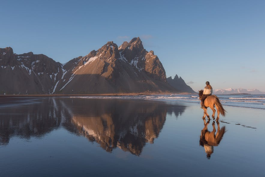 A man on a horse move across a beach towards a mountain - Iceland Photography | Everything You Need To Know