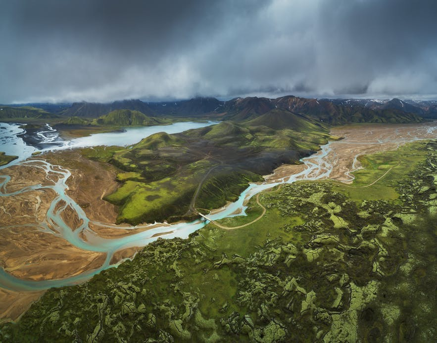 An aerial scene of a landscape hosting a river, mountains and foliage - Iceland Photography | Everything You Need To Know