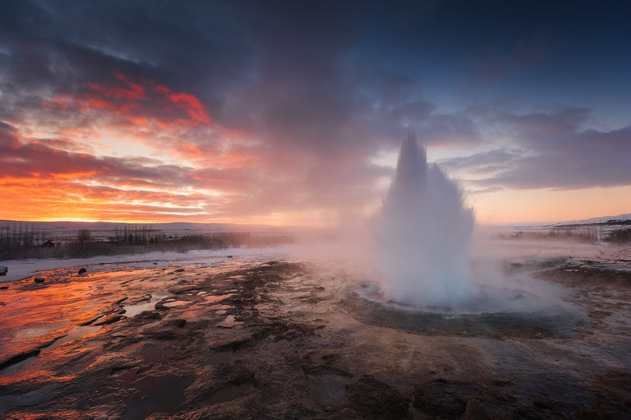 A geyser spurts water during a sunset in a rocky landscape - Iceland Photography | Everything You Need To Know