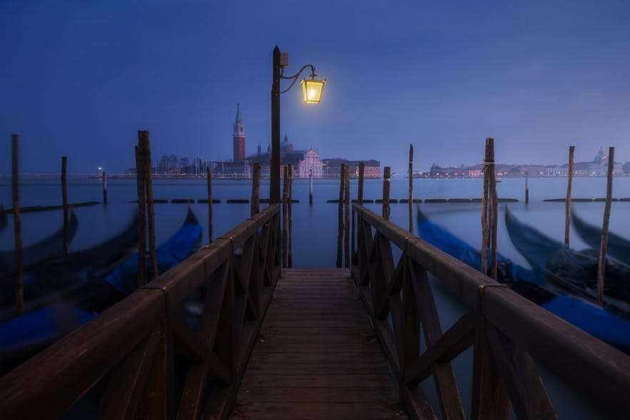 Gondola boats are blurry from moving either side of a walkway on the canals of Venice - landscape Photography | Everything You Need To Know