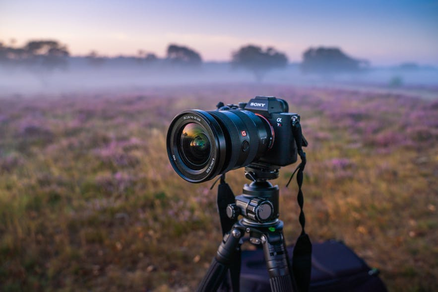 A Sony Mirrorless camera sits on a tripod in the middle of a landscape scene - landscape Photography | Everything You Need To Know