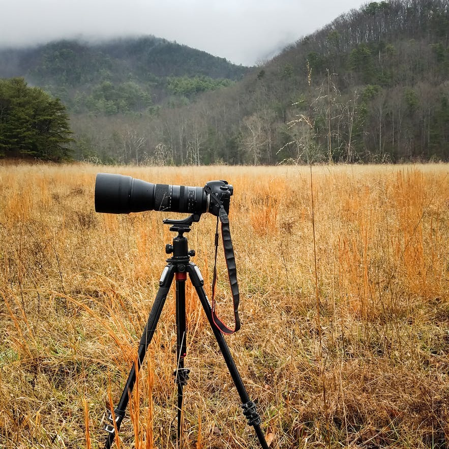 A long telephoto lens sits on a camera in a landscape scene - landscape Photography | Everything You Need To Know