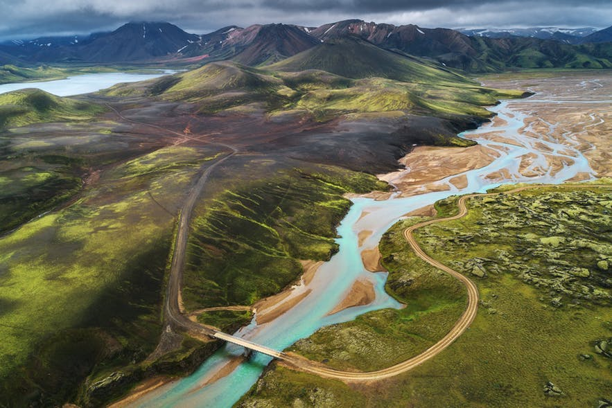 An aerial view of a river and green fields leading to mountains in the background - landscape Photography | Everything You Need To Know