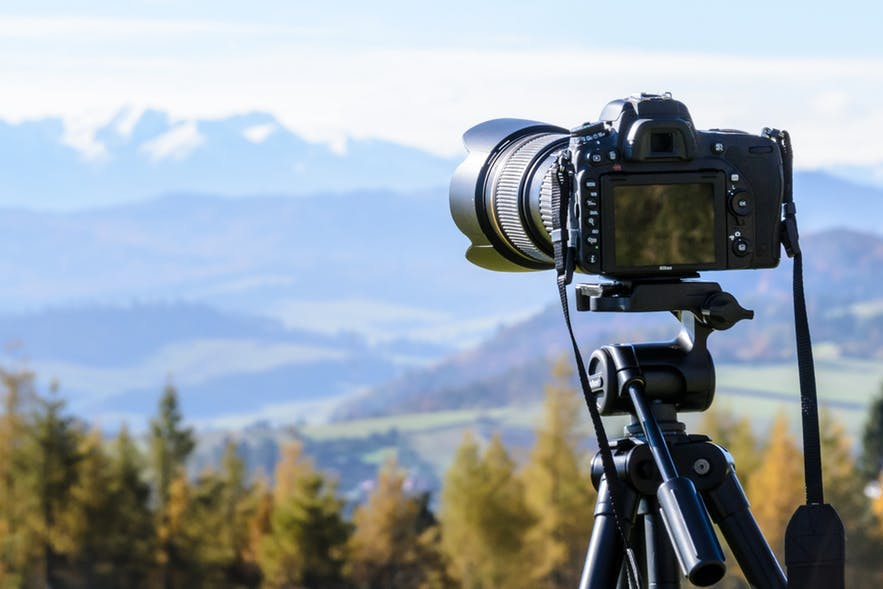 A mirrorless camera sits on a tripod capturing a landscape scene - landscape Photography | Everything You Need To Know
