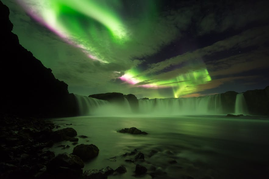 The Aurora Borealis flashes above an under-exposed landscape scene of a waterfall - landscape Photography | Everything You Need To Know