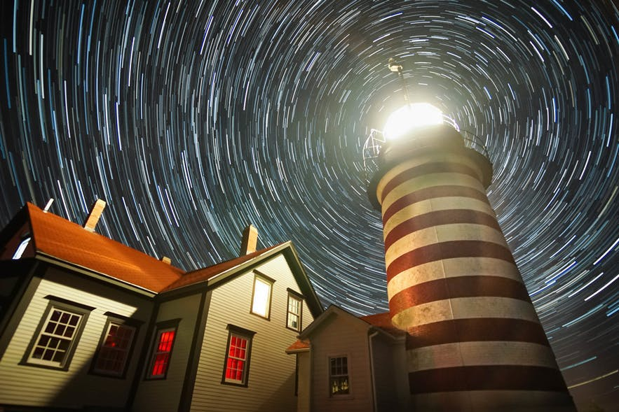 A lighthouse is the centre of stars trailing in the night sky - landscape Photography | Everything You Need To Know