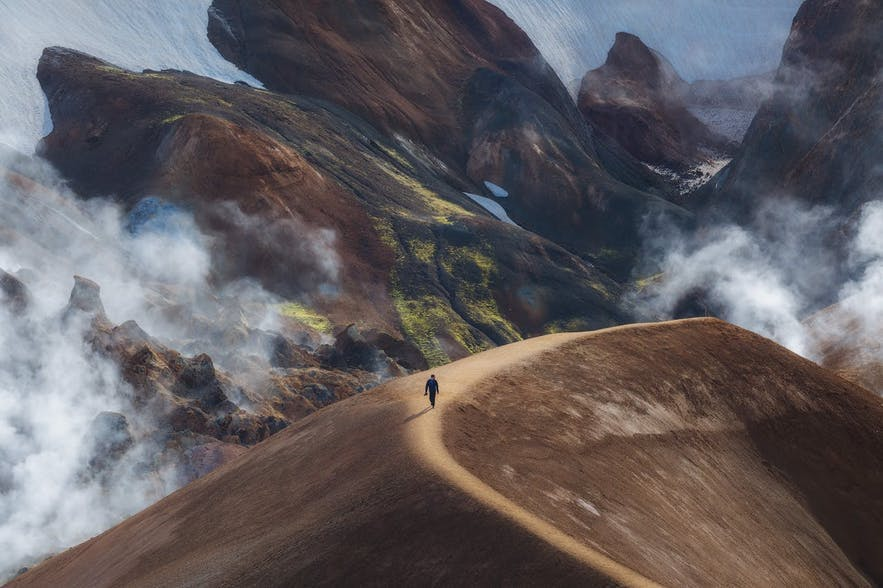 A person walks along the ridge of a mountain while fog and clouds swirl around mountains in the background - landscape Photography | Everything You Need To Know