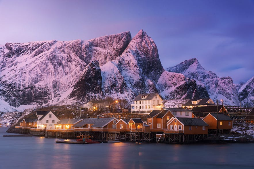 A landscape scene of a small waterside village with mountains in the background - landscape Photography | Everything You Need To Know