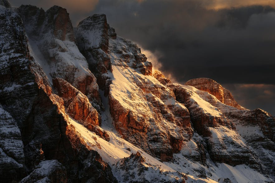 The golden hour light hits the side of a snowy mountain range - landscape Photography | Everything You Need To Know