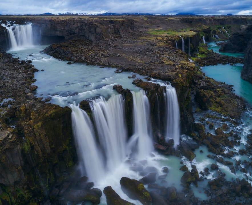 A set of waterfalls in the foreground of a rocky landscape in overcast light - landscape Photography | Everything You Need To Know
