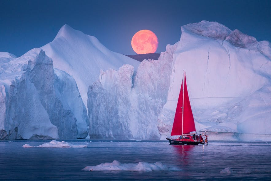 A red boat passes an enormous iceberg as the midnight sun hangs in the distant sky - landscape Photography | Everything You Need To Know