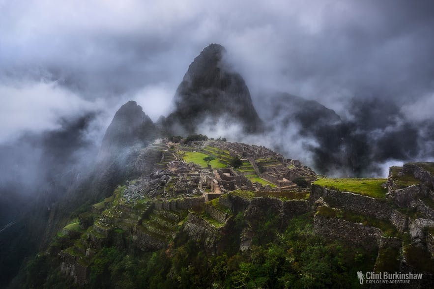 An ancient stone city on a mountain top is surrounded by cloudy fog- landscape Photography | Everything You Need To Know