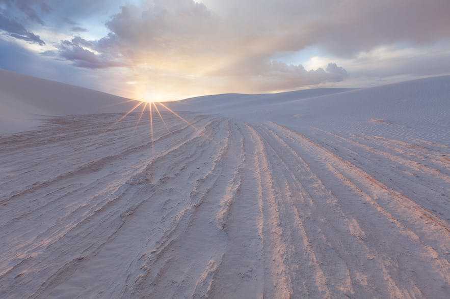 Lines in a snow-covered landscape lead to the rising sun, bursting over the horizon - landscape Photography | Everything You Need To Know
