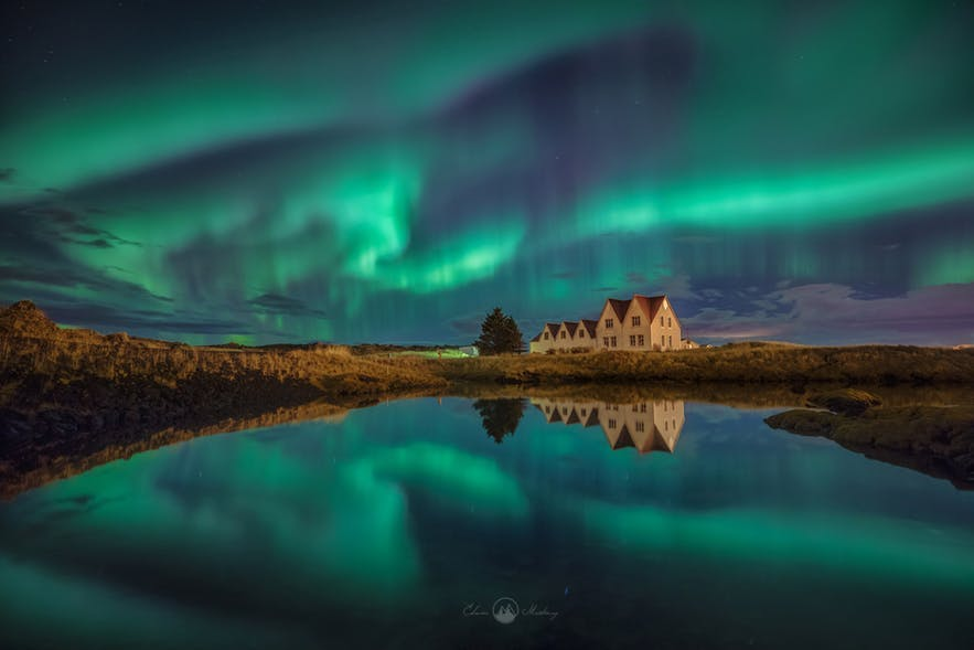 The Aurora curls in the sky above a series of houses in a forest and lake landscape- landscape Photography | Everything You Need To Know