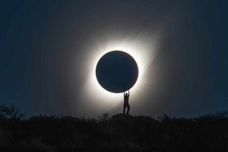 A man stands on a rocky ledge, underneath a solar eclipse - landscape Photography | Everything You Need To Know