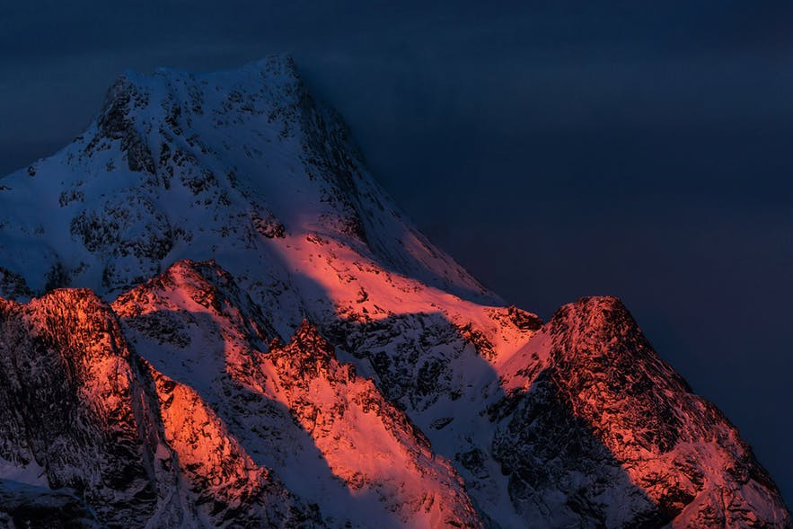 The warm, midnight sun hits the side of a snow-covered mountain - landscape Photography | Everything You Need To Know