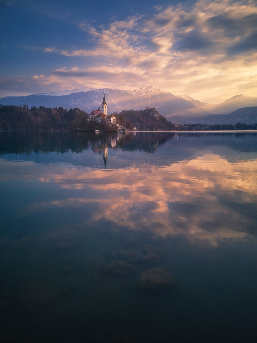 A church on an island is reflected in the mirror-like water of a lake - landscape Photography | Everything You Need To Know