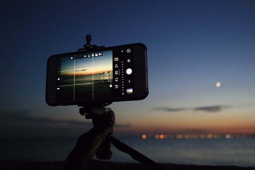 A smartphone sits on a small tripod capturing a nighttime water landscape scene - landscape Photography | Everything You Need To Know