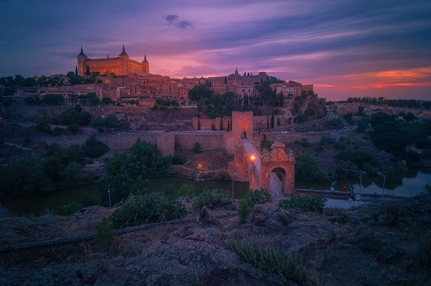 The setting sun adds a pink hue to a castle and gate landscape scene - landscape Photography | Everything You Need To Know