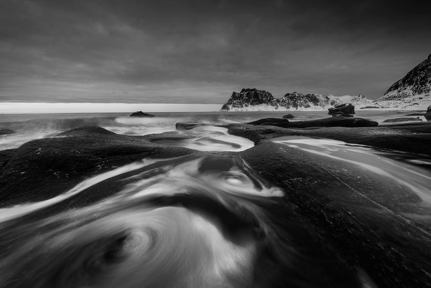 A black and white coastal scene showing blurry water - landscape Photography | Everything You Need To Know