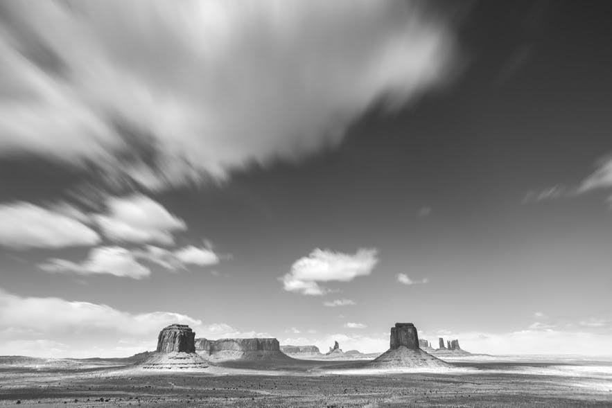 A black and white scene of the desert and rock formations as blurry clouds fly past overhead - landscape Photography | Everything You Need To Know
