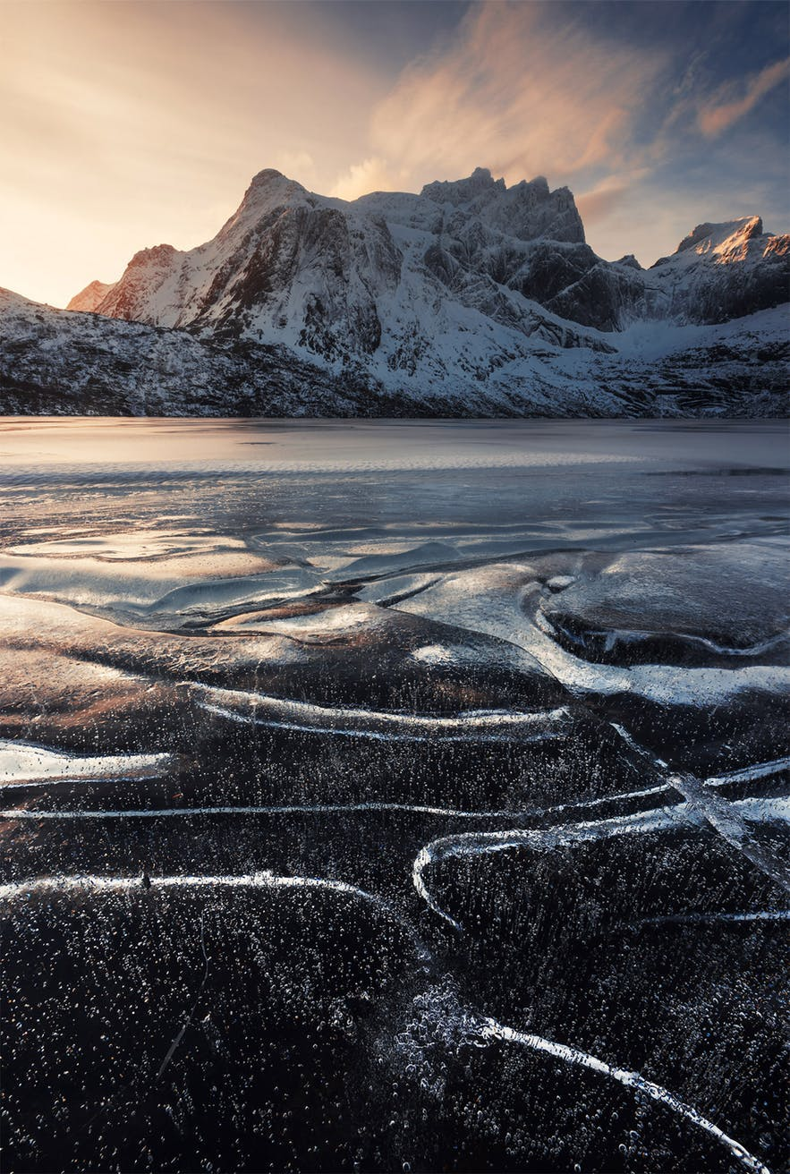 Black, frozen water fills the foreground as a mountain sits in the background - landscape Photography | Everything You Need To Know