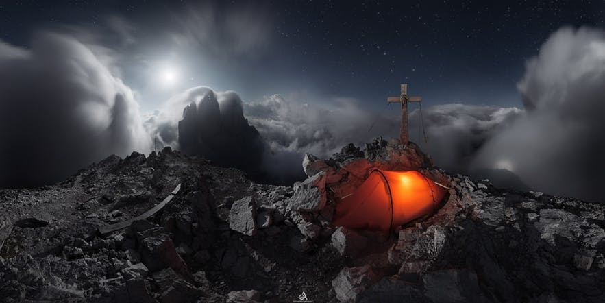 A nighttime panoramic image of a lit-up tent and a cross on the peak of a mountain - landscape Photography | Everything You Need To Know