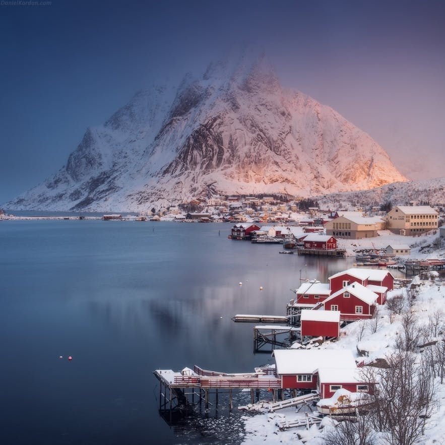 Red coloured houses along the water's edge lead to a snow-covered mountain in the background - landscape Photography | Everything You Need To Know