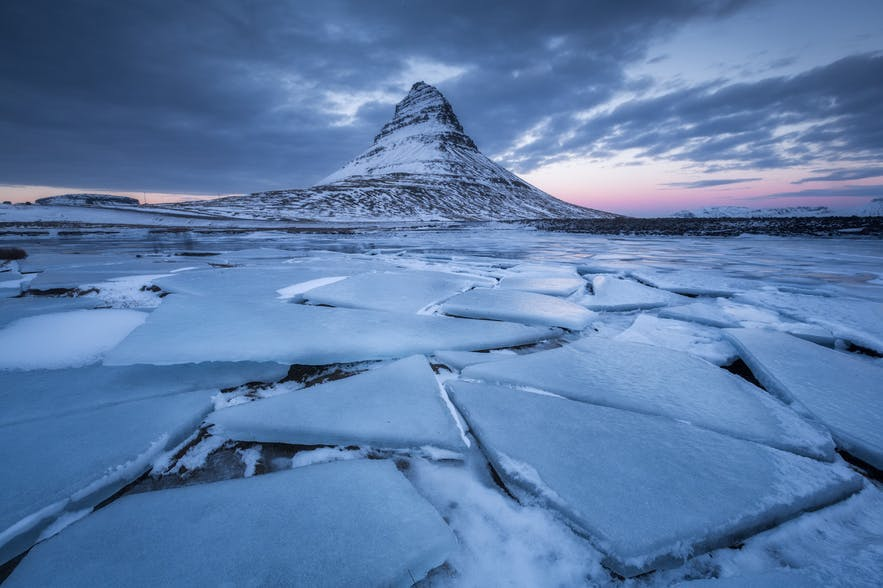 Broken ice sits in the foreground as a mountain lies in the background - landscape Photography | Everything You Need To Know