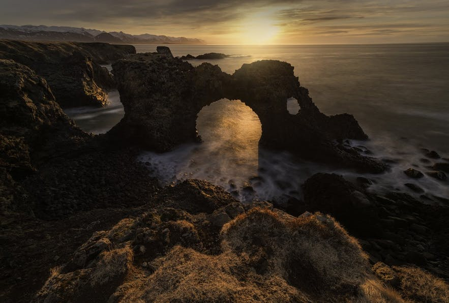 The sunsets behind a coastal rock formation - landscape Photography | Everything You Need To Know