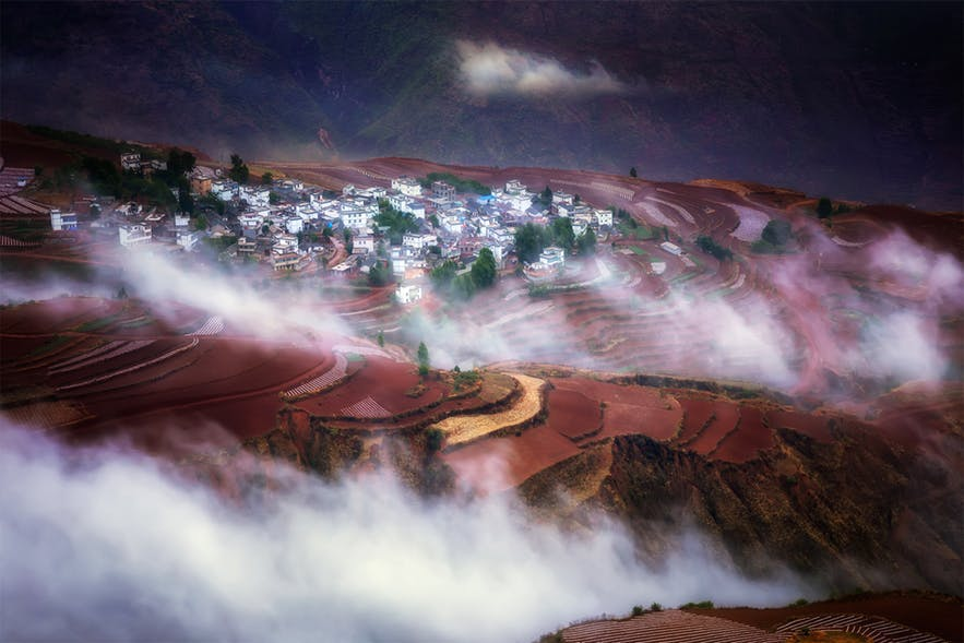 A mountainous village, surrounded by clouds is viewed from above - landscape Photography | Everything You Need To Know