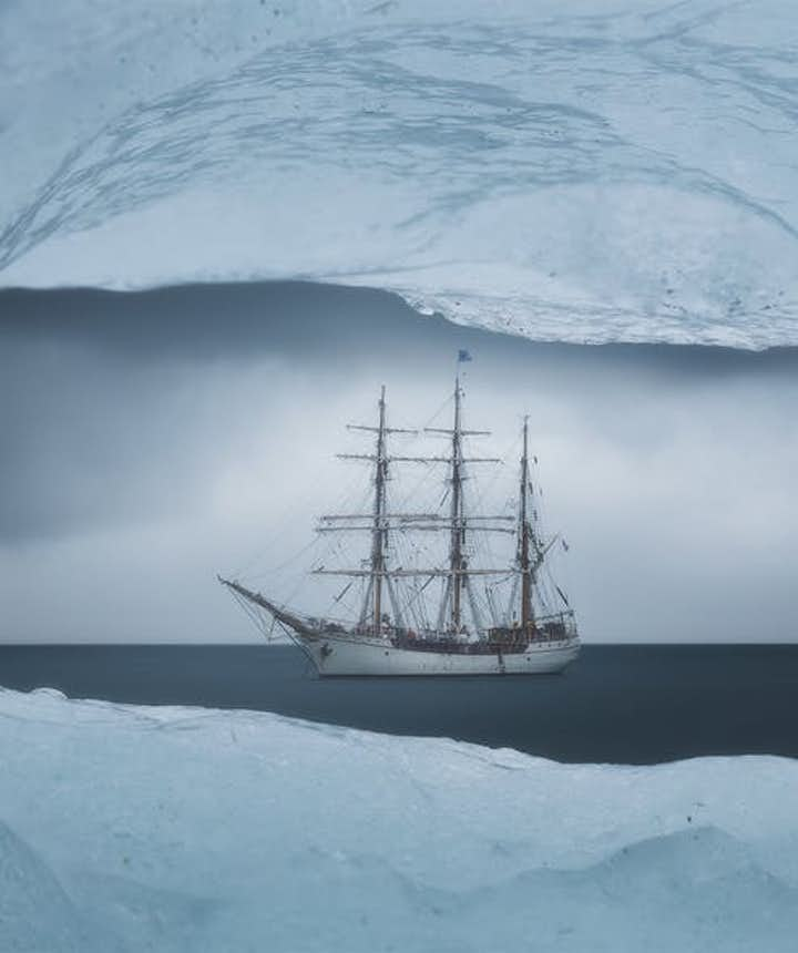 A boat is framed by a window of ice - landscape Photography | Everything You Need To Know