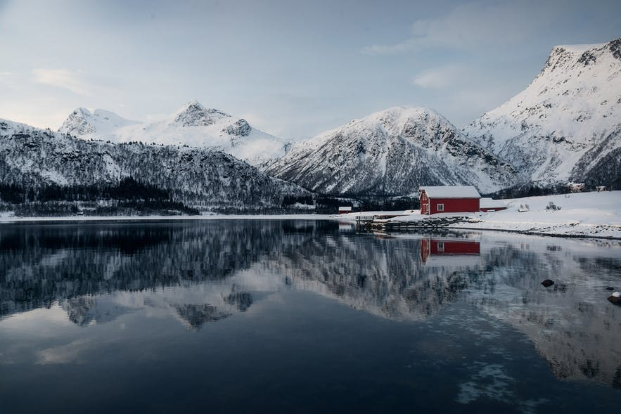 The still water of a lake reflects the snow-covered mountainous and red house scene - landscape Photography | Everything You Need To Know