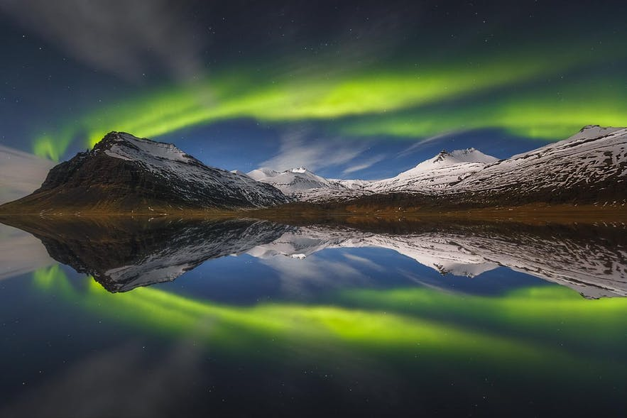 The Aurora dances over a mountainous scene which is reflected in a lake - landscape Photography | Everything You Need To Know