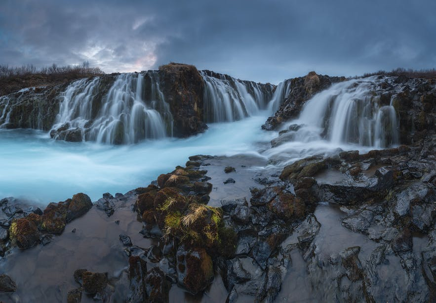 Water trickles off a rocky, blue landscape - landscape Photography | Everything You Need To Know