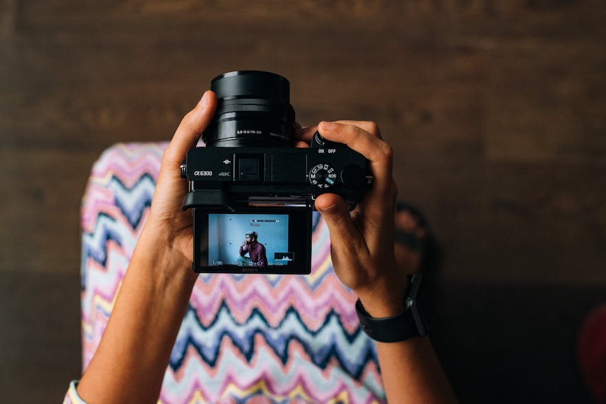 A girl's hands hold a digital camera from a top-down perspective - types of cameras | digital