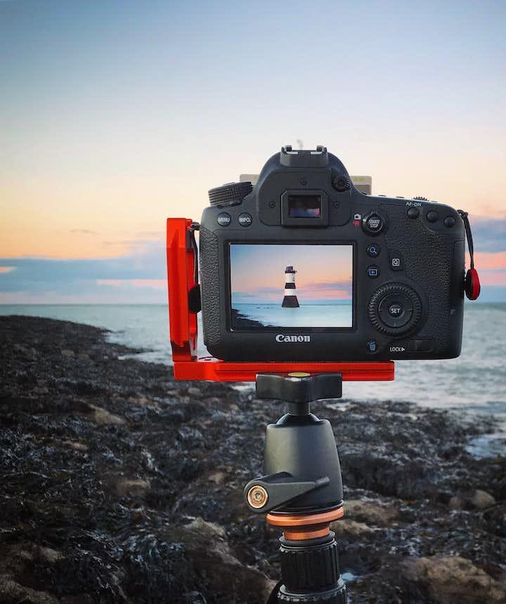 A digital camera sits on a tripod in a coastal scene - types of cameras   digital