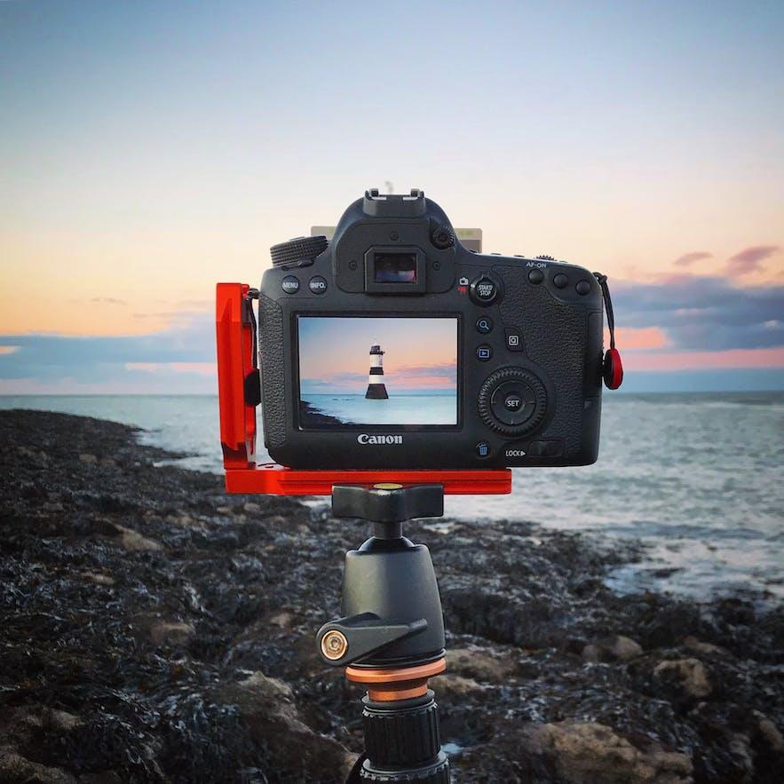 A digital camera sits on a tripod in a coastal scene - types of cameras | digital