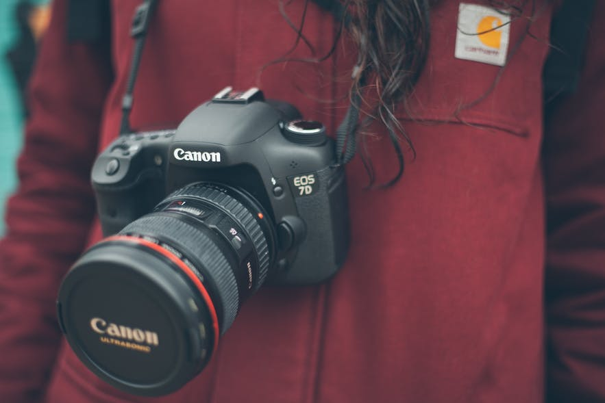 A digital camera hangs around the neck of a person with a red jumper in the background - types of cameras | digital
