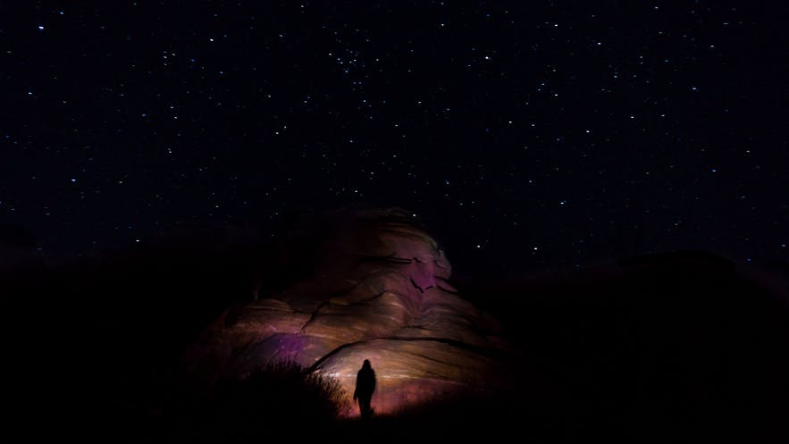 Part of a rocky landscape is lit up behind the photographer during a nighttime shoot   DSLR Accessories
