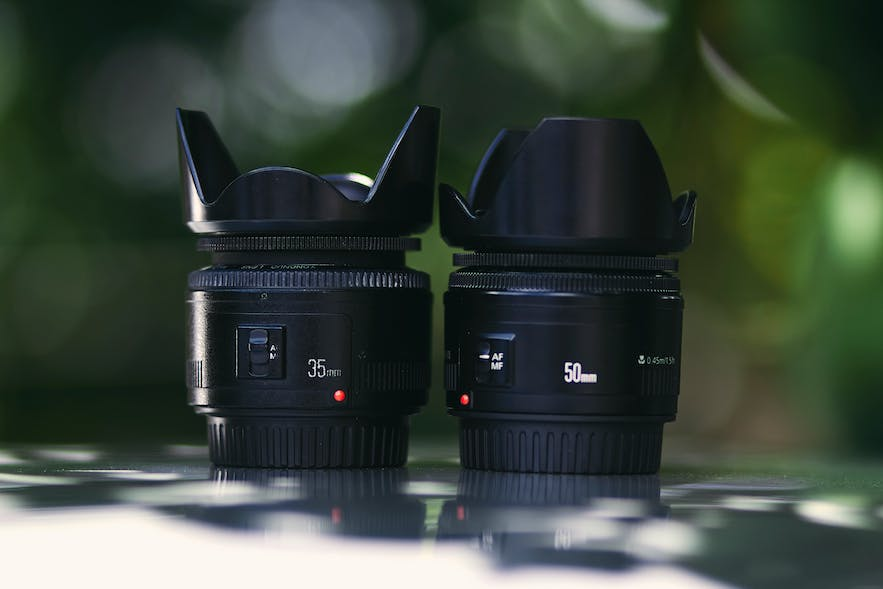 Two lenses with lens hoods sit on a reflective surface   DSLR Accessories