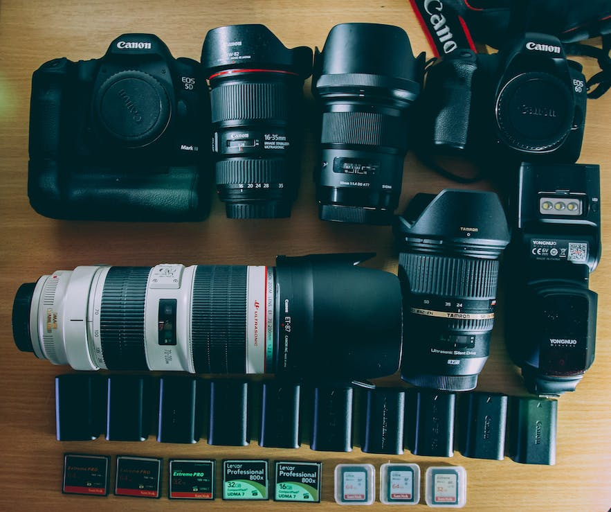 DSLR camera bodies and lenses are laid out on a wooden surface, viewed from top-down    DSLR Accessories