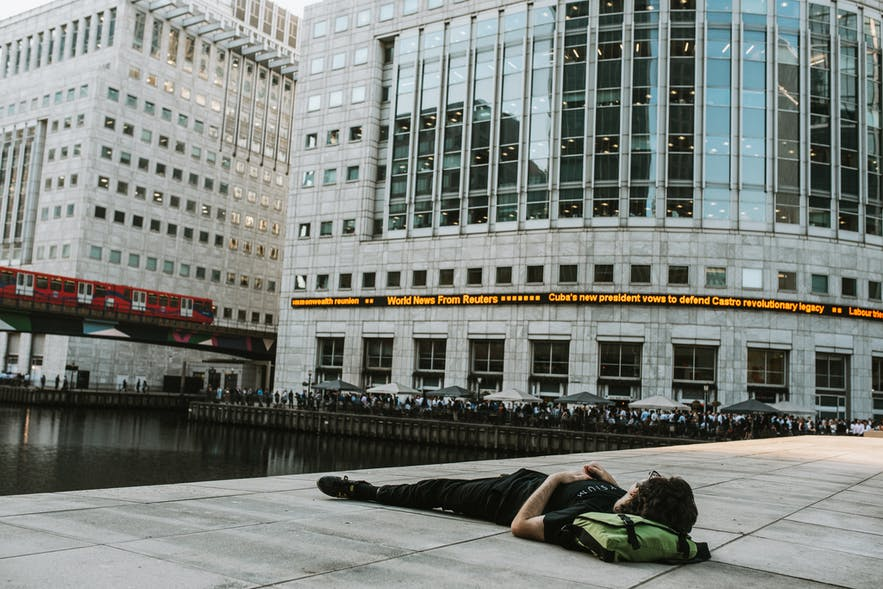 A man laying down in Canary Wharf, London.