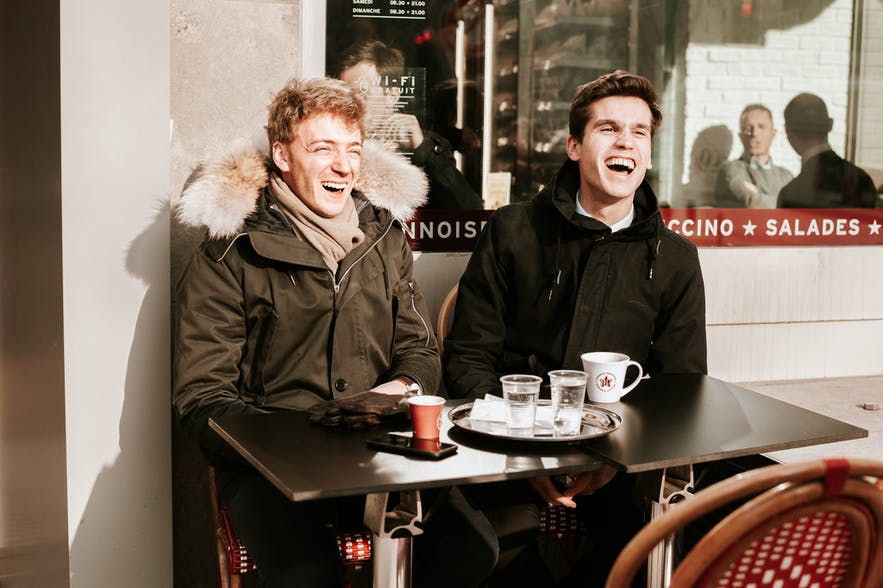 Two young men sat outdoors at a coffee shop.