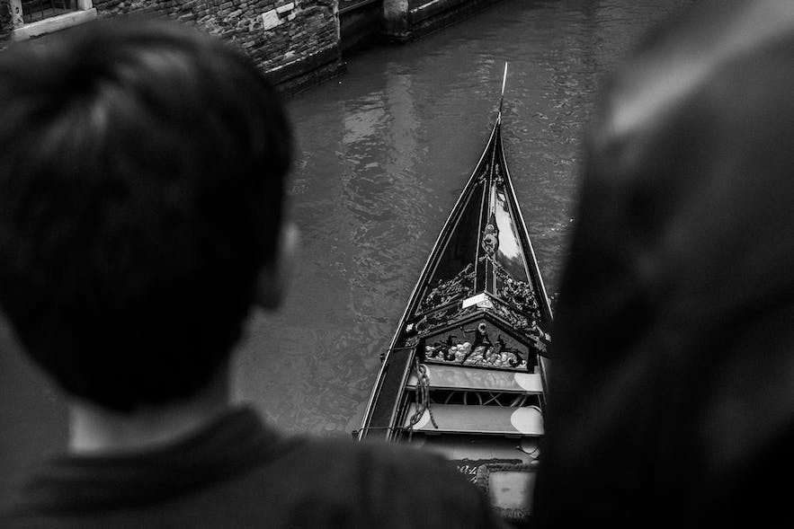 A boy and father watching a Venetian gondola.
