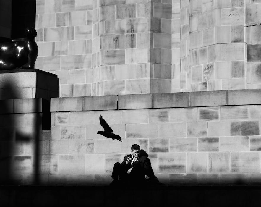 A man sat down on a bench in a city having lunch.
