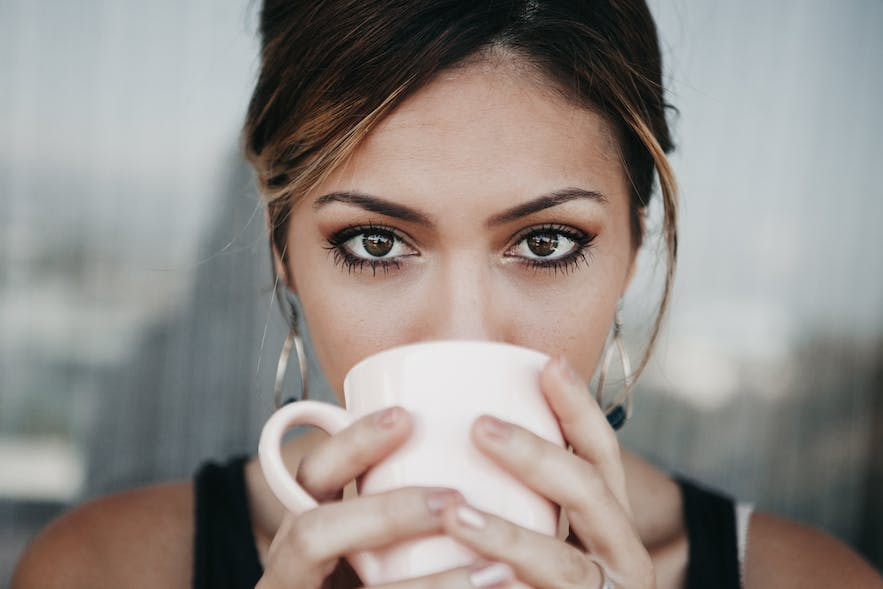 A woman drinking from a coffee cup.