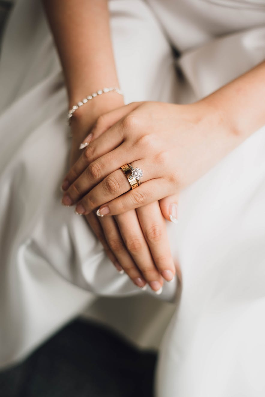 A bride sat with hands on her knees, showing her rings.