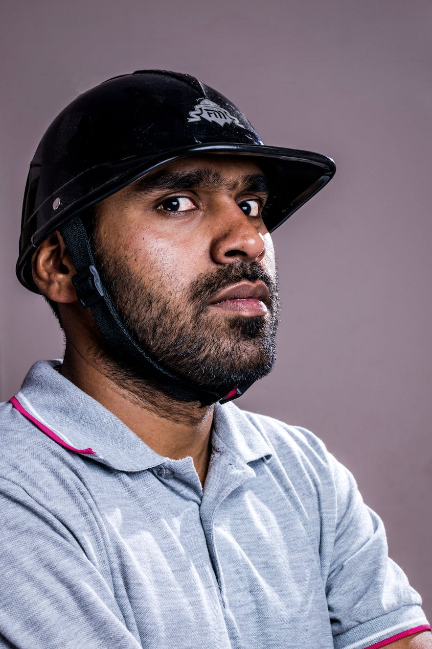 A man in a polo helmet and polo shirt looks at the camera with a sideways glance